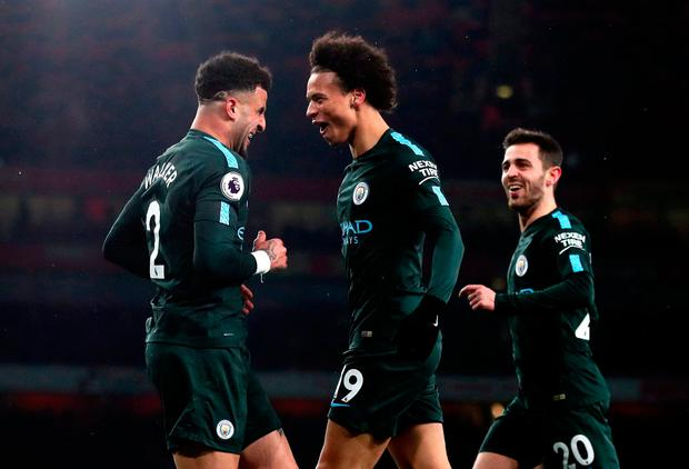 Manchester City's Leroy Sane (centre) celebrates scoring his side's third goal of the game with Kyle Walker (left) and Bernardo Silva during the Premier League match at the Emirates Stadium, London. Nick Potts/PA Wire.