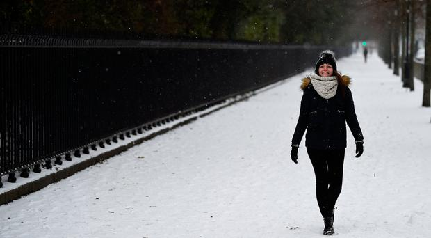 A woman walks in the snow on St. Stephen's Green in the centre of Dublin. REUTERS/Clodagh Kilcoyne