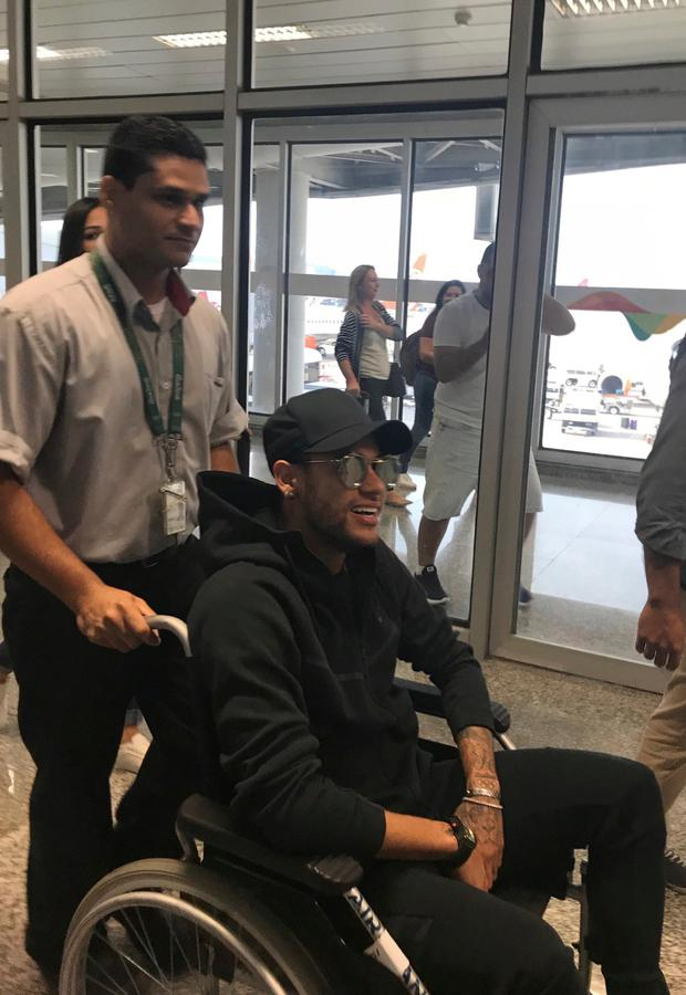 In this photo provided by Claire Dorland Clauzel, Brazilian soccer player Neymar is pushed in a wheelchair after arriving to the airport in Rio de Janeiro, Brazil. (Claire Dorland Clauzel via AP)