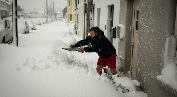 Despite only wearing shorts James Butterworth uses cardboard to dig himself out of the Snow drifts on Harbour road, Arklow, Co Wicklow. Photograph: Garry O'Neill