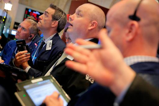 Traders work on the floor at the New York Stock Exchange (NYSE) in Manhattan