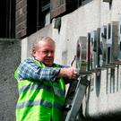 Workman Ken Glennon removes Anglo Irish Bank signage outside its former headquarters on St Stephen's Green, Dublin in 2011. Photo: Gareth Chaney / Collins
