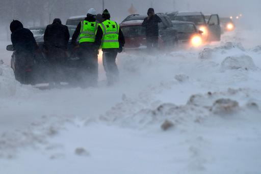 People try to push a car that hadve become stuck in heavy snow during a blizzard in Dublin earlier this week. Photo: Clodagh Kilcoyne