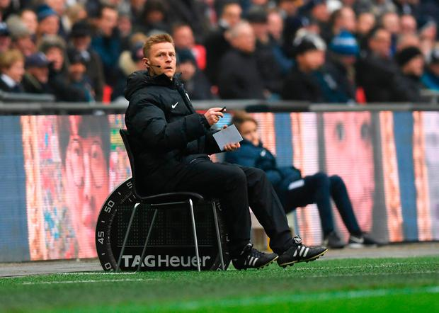Injured referee Mike Jones sits on a chair pitchside as he operates as fourth official Photo: Getty