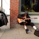 AMERICAN DREAM: A homeless man plays his guitar in the street in the Mission District in San Francisco.