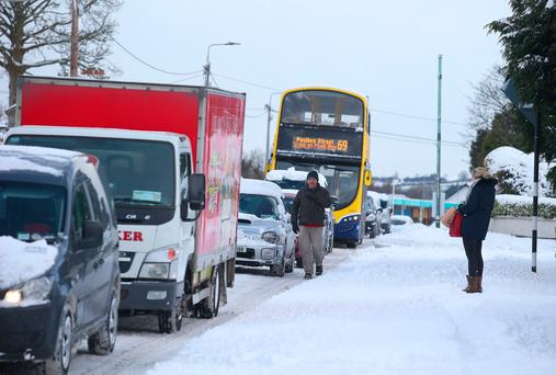 A woman waits for the bus as man walks past traffic in a snow covered Rathcoole, Co. Dublin. Photo: Damien Eagers
