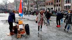 A hot-chocolate seller watches as ice skaters skate and walk on the frozen Prinsengracht canal during icy weather in Amsterdam. Photo: Reuters