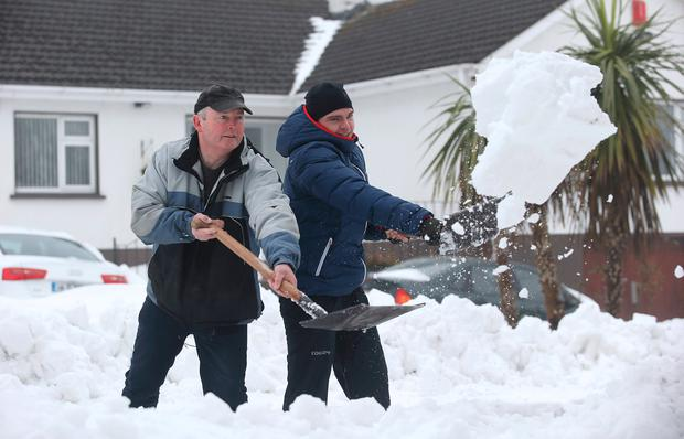 Tommy Thompson and his son Andrew shovel snow in Kilteel Road, Co Dublin