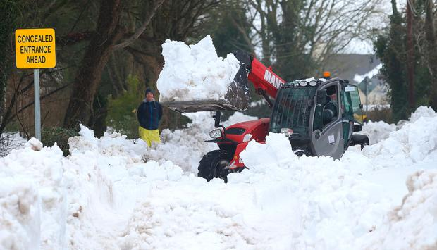 Digger driver Patsy Dunne clears snow from Kilteel Road as Damien Lee looks on.
