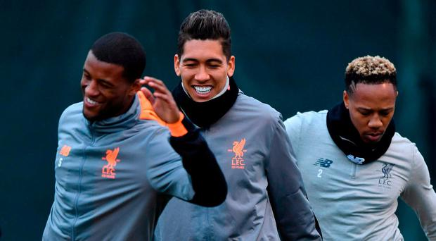 Liverpool players (l-r) Georginio Wijnaldum, Roberto Firmino and Nathaniel Clyne go through their stretching routine at Melwood yesterday. Photo: Anthony Devlin/AFP/Getty Images