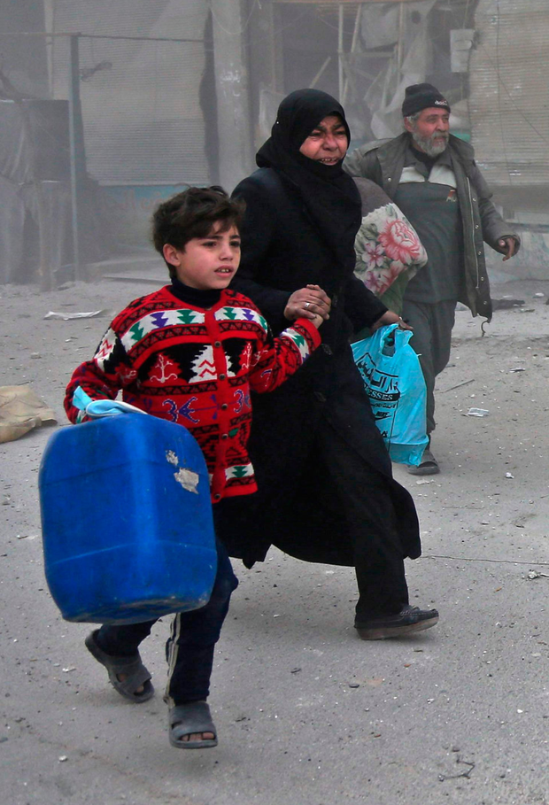 Syrians run for cover in Eastern Ghouta yesterday. Photo: Getty Images