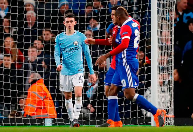 Manchester City's Phil Foden appears dejected as FC Basel players celebrate their second goal Photo: Martin Rickett/PA Wire