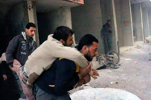 This photo released by the Syrian Civil Defense White Helmets, which has been authenticated based on its contents and other AP reporting, shows a member of the Syrian Civil Defense group carrying a man who was wounded after airstrikes and shelling hit in Ghouta, a suburb of Damascus, Syria, Wednesday, March. 7, 2018. (Syrian Civil Defense White Helmets via AP)