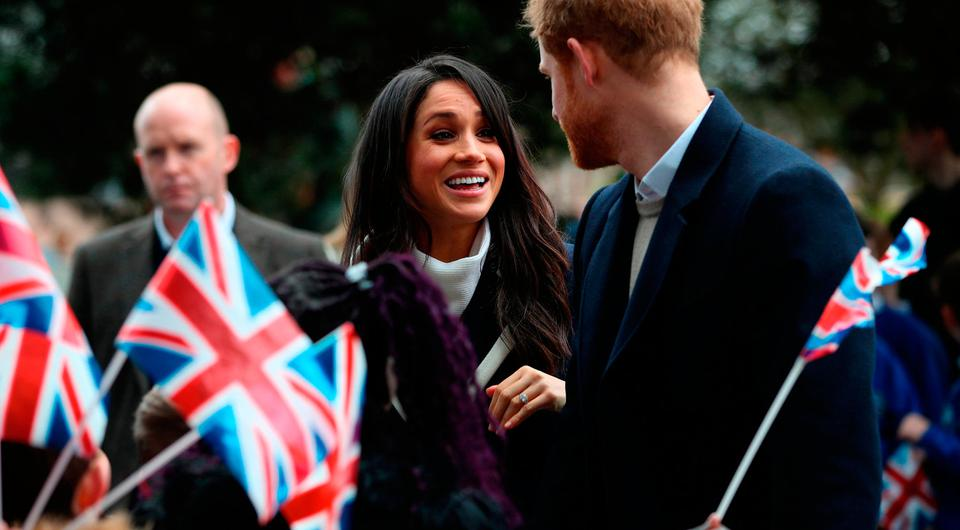 Britain's Prince Harry (R) and his fiancee US actress Meghan Markle (L) greet well-wishers as they arrive at Millennium Point to attend an event hosted by social enterprise Stemettes to celebrate International Women's Day in Birmingham on March 8, 2018