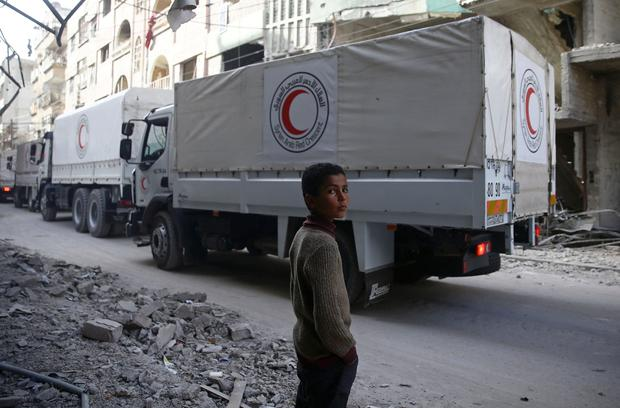 A boy stands as an aid convoy of Syrian Arab Red Crescent drives through the besieged town of Douma, Eastern Ghouta, Damascus, Syria March 5, 2018. REUTERS/Bassam Khabieh