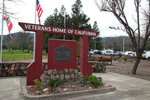 Media trucks stage at the entrance to the Veterans Home of California in Yountville, Calif. (AP Photo/Ben Margot)