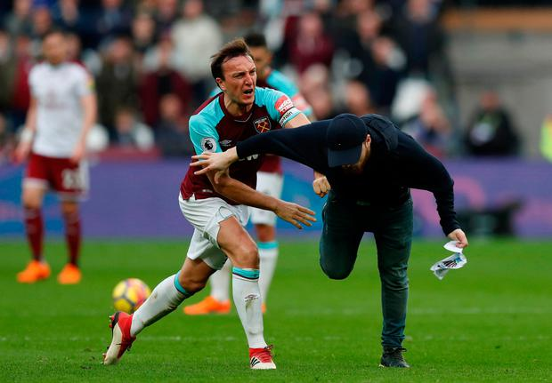 West Ham United's Mark Noble clashes with a fan who has invaded the pitch Action Images via Reuters/Peter Cziborra