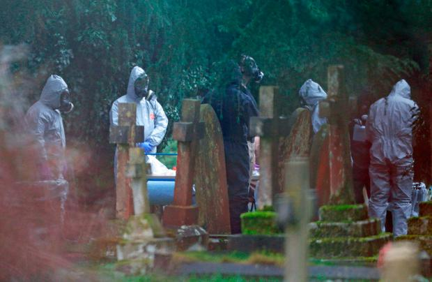 Forensic officers in gas masks at the cemetery where former Russian double agent Sergei Skripal's wife and son were laid to rest. Photo: PA Wire