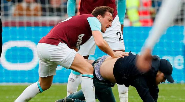 West Ham United's Mark Noble clashes with a fan who invades the pitch. REUTERS/David Klein