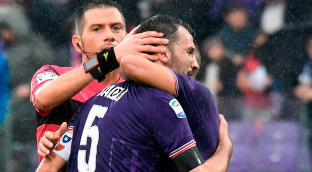 Fiorentina's midfielder and new captain Milan Badelj (C) reacts as referee Fabrizio Pasqua and Fiorentina's defender Vincent Laurini (R) comfort him