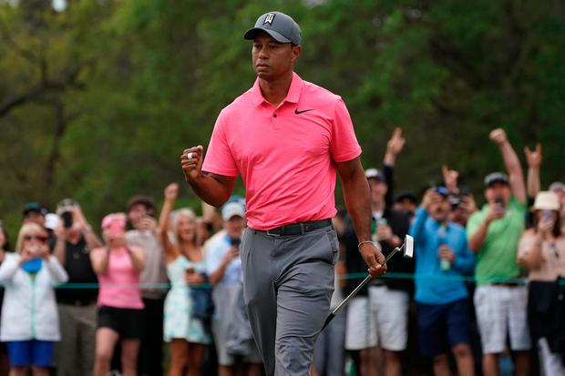 Tiger Woods pumps his fist after making a birdie putt