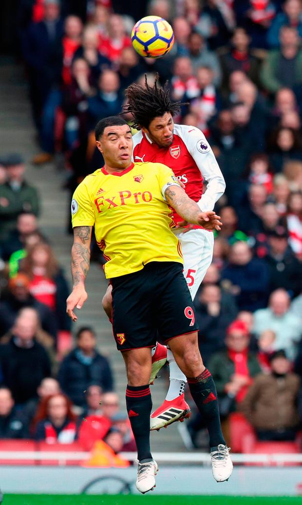 Arsenal's Mohamed Elneny (right) and Watford's Troy Deeney battle for the ball. Photo credit: Jonathan Brady/PA Wire