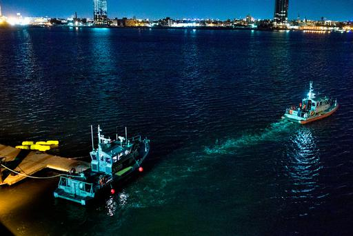 Yellow buoys that a New York police officer said are suspending a helicopter that crashed into the East River float next to a NYPD police boat at a pier in New York on Sunday, March 11, 2018. (AP Photo/Andres Kudacki)