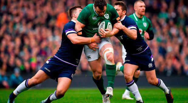Cian Healy of Ireland is tackled by Huw Jones, left, and Greig Laidlaw of Scotland