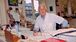 French fashion designer Hubert de Givenchy poses at the office of his fashion house in Paris