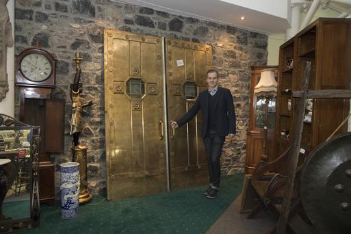 Antiques expert Niall Mullen pictured with the bronze doors from Howl At The Moon nightclub Picture: Michael Donnelly