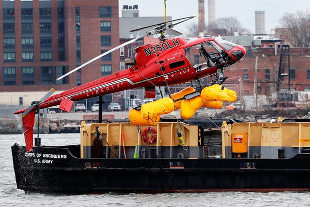 A helicopter is hoisted by crane from the East River onto a barge in New York. (AP Photo/Mark Lennihan)