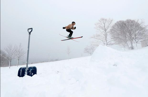 Wesley Miller performs a 360 during a nor'easter, Thursday, March 8, 2018, in Portland, Maine. Miller and some friends built the jump while enjoying a snow day from school due to the storm. (AP Photo/Robert F. Bukaty)