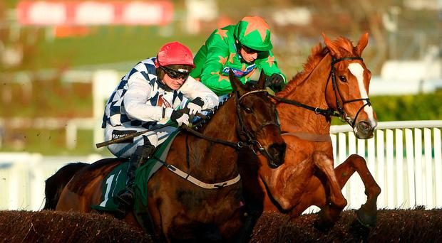 Rathvinden, left, with Patrick Mullins up, leads Ms Parfois, with William Biddick up, on their way to winning the National Hunt Steeple Chase Challenge Cup on Day One of the Cheltenham Racing Festival at Prestbury Park in Cheltenham, England. Photo by Ramsey Cardy/Sportsfile