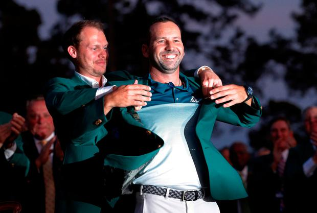 Sergio Garcia of Spain smiles as he is presented with the green jacket by Danny Willett after winning the 2017 Masters golf tournament