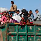 A family sits on a truck with their belongings north-east of Afrin, Syria, yesterday. Photo: Reuters/Khalil Ashawi