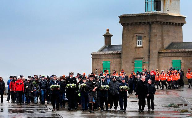 Members of the search and rescue agencies carry wreaths alongside family members at Blacksod lighthouse. Photo: Steve Humphreys