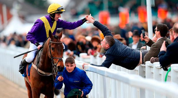 Jockey Mark Walsh celebrates with a punter after his victory aboard Bleu Berry in the Coral Cup PA. Photo: Mike Egerton/PA Wire