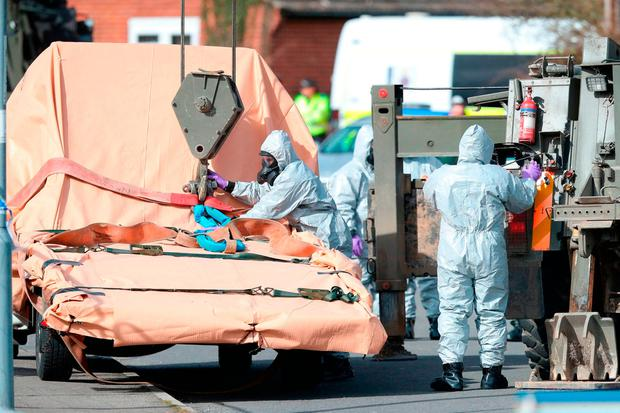 Soldiers wearing protective clothing prepare to lift a recovery vehicle as the investigation into the suspected nerve agent attack on Russian double agent Sergei Skripal continues Photo: Andrew Matthews/PA