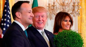 US President Donald Trump (C) picks up a bowl of shamrocks as Ireland's Prime Minister Leo Varadkar (L) and US first lady Melania Trump look on in the East Room of the White House in Washington, DC. / AFP PHOTO / Mandel NGANMANDEL NGAN/AFP/Getty Images