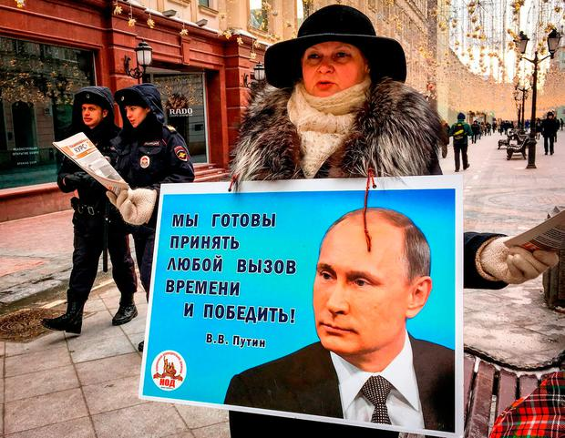 An activist distributes leaflets in support of incumbent Vladimir Putin in downtown Moscow, ahead of the upcoming Russian presidential elections. Photo: Getty Images