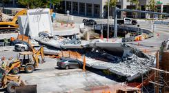 Workers remove debris from the collapsed pedestrian bridge at Florida International University in Miami. Photo: Reuters