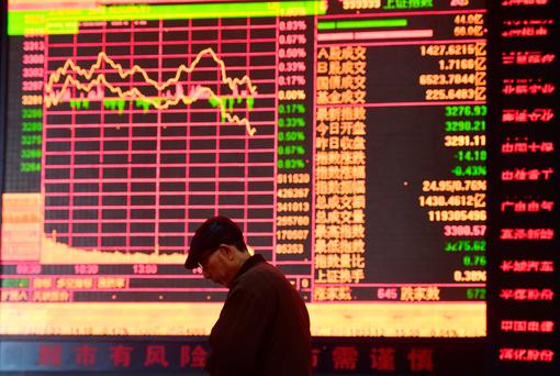 A man is seen against an electronic board showing stock information at a brokerage house in Fuyang, Anhui province, China