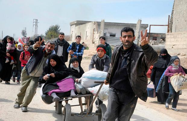 This photo released by the Syrian official news agency SANA, shows Syrian civilians with their belongings flashing the victory sign, as they flee from fighting between the Syrian government forces and rebels, in Hamouria in eastern Ghouta, a suburb of Damascus, Syria, Thursday, March. 15, 2018. (SANA via AP)