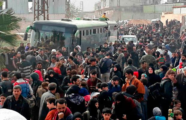 This photo released by the Syrian official news agency SANA, shows Syrian civilians with their belongings, fleeing from fighting between the Syrian government forces and rebels, in eastern Ghouta, a suburb of Damascus, Syria, Thursday, March. 15, 2018. (SANA via AP)