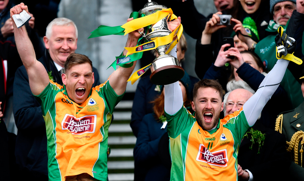 Corofin joint captains Ciarán McGrath (left) and Micheál Lundy lift the Andy Merrigan Cup. Photo: Sportsfile
