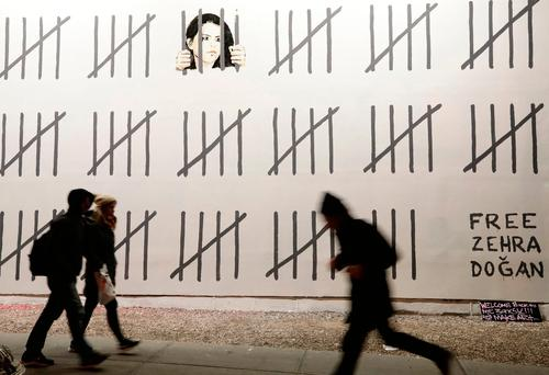 People pass by part of a mural by British graffiti artist Banksy protesting the imprisonment of Turkish artist Zehra Dogan (AP Photo/Frank Franklin II)