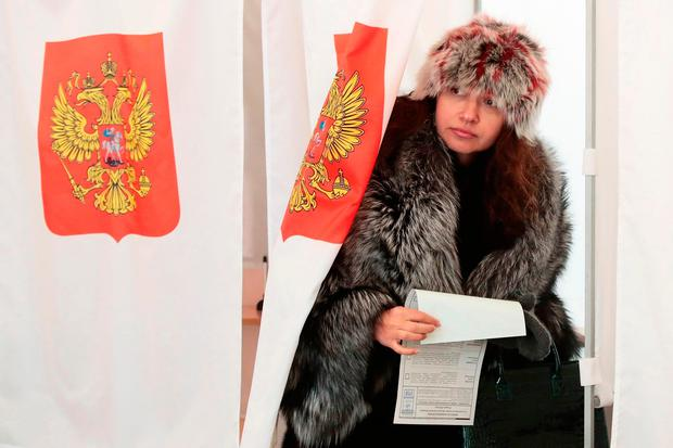 A woman exits a polling booth as she prepares to cast her ballot in the presidential election in Moscow, Sunday, March 18, 2018.(AP Photo/Denis Tyrin)