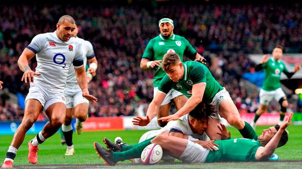 Garry Ringrose dives across Rob Kearney and England's Anthony Watson to score Ireland's first try as Mike Brown looks on. Photo: Ramsey Cardy/Sportsfile