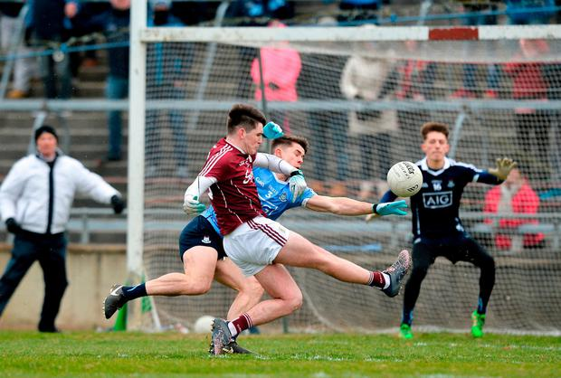 Galway's Barry McHugh gets a shot away despite the efforts of David Byrne. Photo: Ray Ryan/Sportsfile