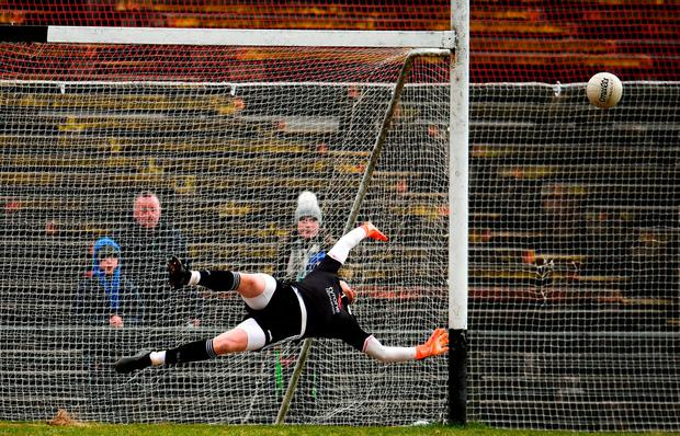 Tyrone goalkeeper Mickey O'Neill dives to see Conor Loftus' penalty sail wide. Photo: Sam Barnes/Sportsfile